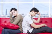 Couple Stress Sitting On Red Sofa