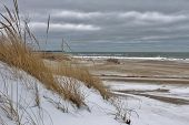 stock photo of coast guard  - Sand dune stands guard over a windswept winter beach - JPG