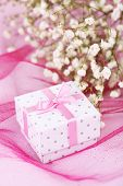 Flowers and gift box on pink background