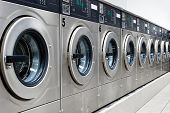 stock photo of oversize load  - A row of industrial washing machines at a public laundromat - JPG