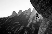 stock photo of mountain-climber  - a rock climber stuggles to hold on - JPG