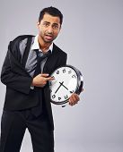stock photo of pressure point  - Worried businessman pointing to his clock on gray background - JPG