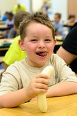 picture of pre-teen boy  - Happy child eating healthy lunch in busy school cafeteria - JPG