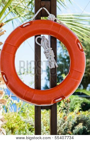 Orange Life Buoy With Rope Hanging Around The Pool