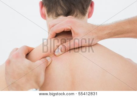 Close-up rear view of a shirtless man being massaged by a physiotherapist over white background