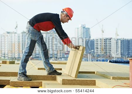 Roofer builder worker installing roof insulation material