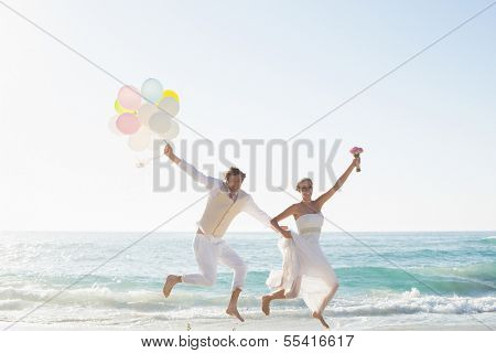 Newlyweds having fun holding balloons at the beach
