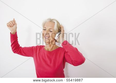 Happy senior woman listening music over white background