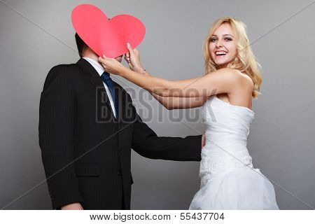 Portrait Of Happy Bride And Groom With Red Heart On Gray