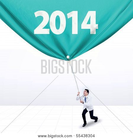 Male Doctor Pulls A Banner Of New Year 2014