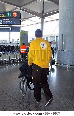 Porter pushing wheelchair at airport.