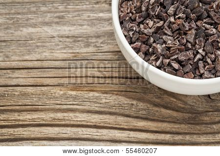 Raw cacao nibs in a small ceramic bowl against grained wooden background