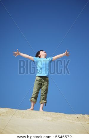 Boy Stands On Sand And Looks Upwards