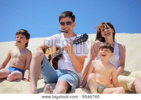 Guy In Sunglasses Plays Guitar And  Lip Accordion  With Children