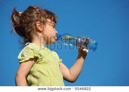 Girl Drinks Water From  Plastic Bottle Against Blue Sky