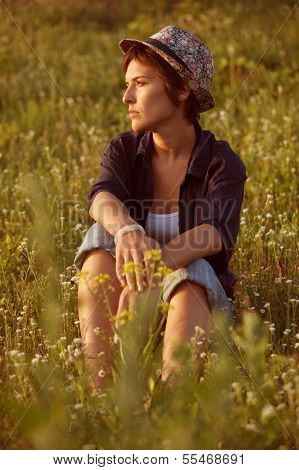 Woman In Hat Sitting Among Wildflowers