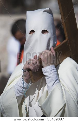 Penitent carried a wooden cross in a procession of Holy week