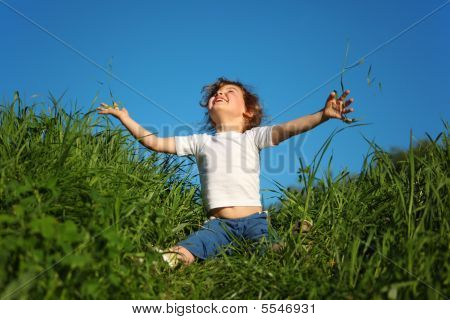 Little Girl Sits In Grass And Looks Upwards
