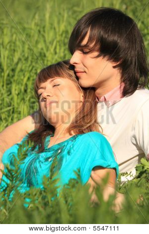 Girl Lies On Guy Sitting In Grass