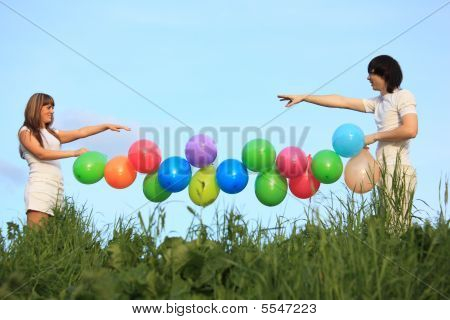 Girl And Guy Hold Garland Of Multicoloured Balloons In  Grass Ag