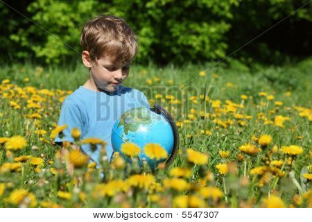 Boy With Globe On Meadow Among Blossoming Dandelions