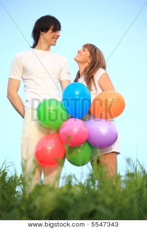 Girl And Guy Stand In Grass With Multicoloured Balloons