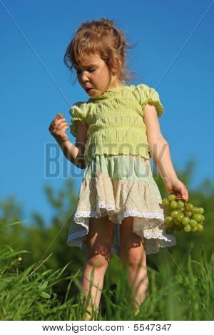 Girl Eats Grape In Grass Against Blue Sky