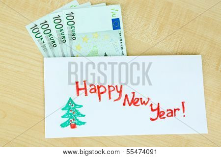 Euro banknotes in envelope as gift at New year on wooden table close-up