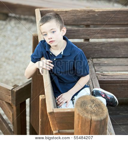 Very Sad Handsome Boy Sitting In The Park