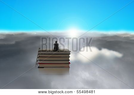 Businessman Sitting On Stack Of Books Over Cloudy Face Sun