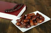 Composition with holy book,rosary and dates palm, on wooden background