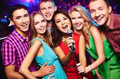 stock photo of karaoke  - Portrait of happy girls and guys singing in microphone in the karaoke bar - JPG