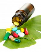 Ginkgo biloba leaves and medicine bottle with pills isolated on white