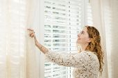 stock photo of redhead  - Happy woman looking out big bright window with curtains and blinds - JPG
