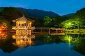 stock photo of gazebo  - Nice japanese wooden gazebo is shortly after the sunset reflecting in the water - JPG