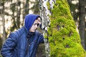 stock photo of pain-tree  - Sorrowful boy leaning on a tree in the forest - JPG