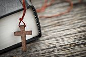 stock photo of praying  - Closeup of wooden Christian cross necklace next to holy Bible - JPG