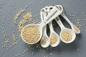 stock photo of quinoa  - Quinoa grain in porcelain measuring spoons on gray background - JPG