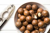 pic of nutcracker  - top view of macadamia nuts with nutcracker on white wooden table - JPG