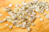 stock photo of uncut  - A pile of white grey uncut and rough diamonds on birch wood - JPG