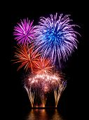image of firework display  - Magnificent fireworks display with happy colors on black background reflected on water - JPG