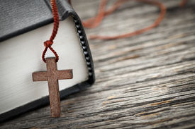 picture of holy  - Closeup of wooden Christian cross necklace next to holy Bible - JPG