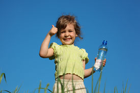 picture of drinking water  - girl in grass with plastic bottle with water shows gesture by finger - JPG