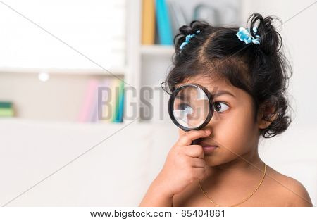 Child at home. Cute Indian girl peeking through magnifying glass.