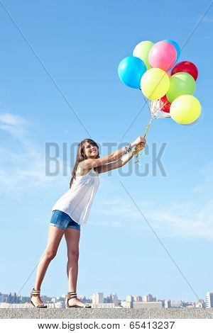 Happy young woman flying away with balloons