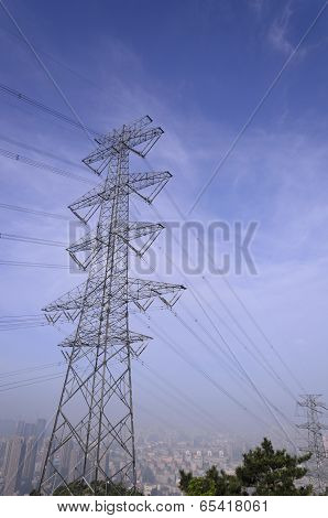 Power-line transmission towers stand on a hill with cloudy sky.
