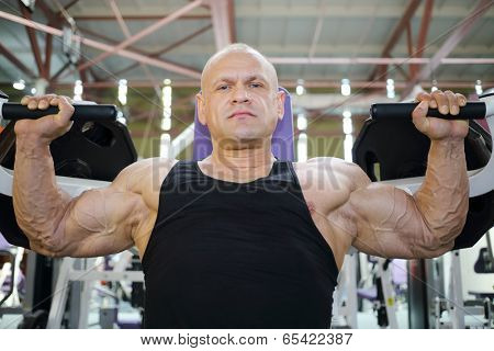 Bodybuilder in black jersey trains on exercise machine in gym hall and looks at camera