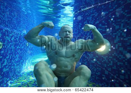 Bodybuilder in swimming trunks sits on bottom of pool underwater with pure water