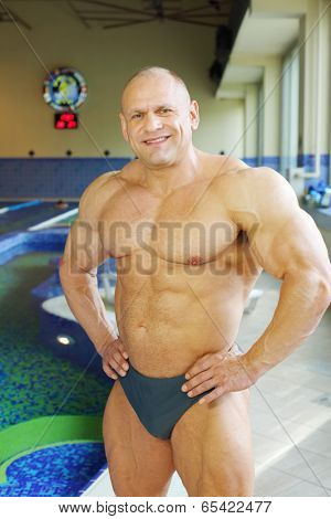 Happy bodybuilder in swimming trunks stands near indoor pool of gym hall