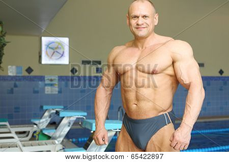 Smiling bodybuilder stands near indoor pure pool before swimming